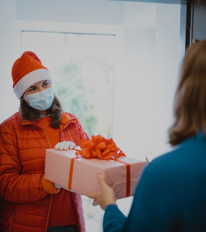 woman giving gift in face mask
