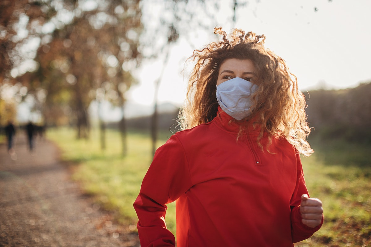A woman with curly hair runs on a country road. Women logged significantly more workouts in 2020 over 2019, especially compared to men.