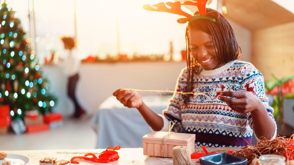 A woman in reindeer antlers decorates her Christmas gift using ribbons and string