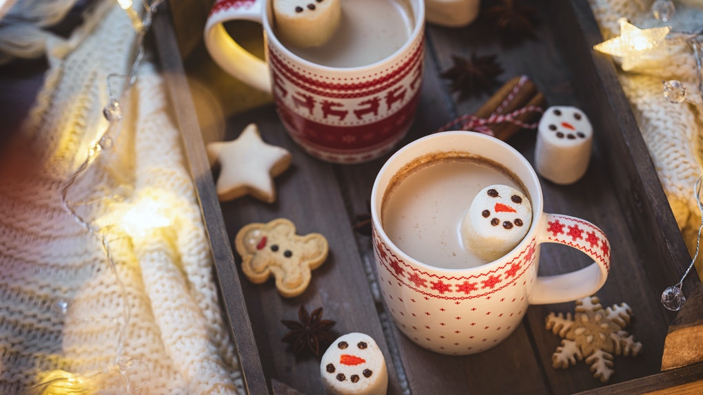 Two mugs of hot chocolate with snowman marshmallows are placed on a festive tray.