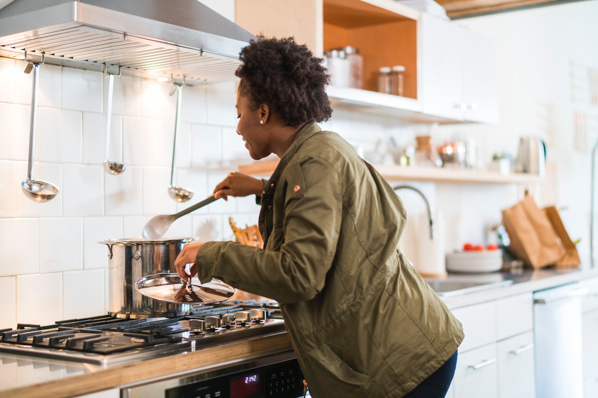 A young Black woman checks and stirs a pot of homemade soup on a snow day.