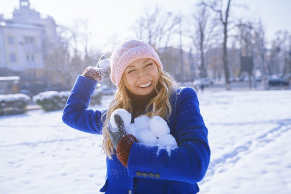 A happy blonde woman in a blue pea coat holds snowballs on a snowy day.