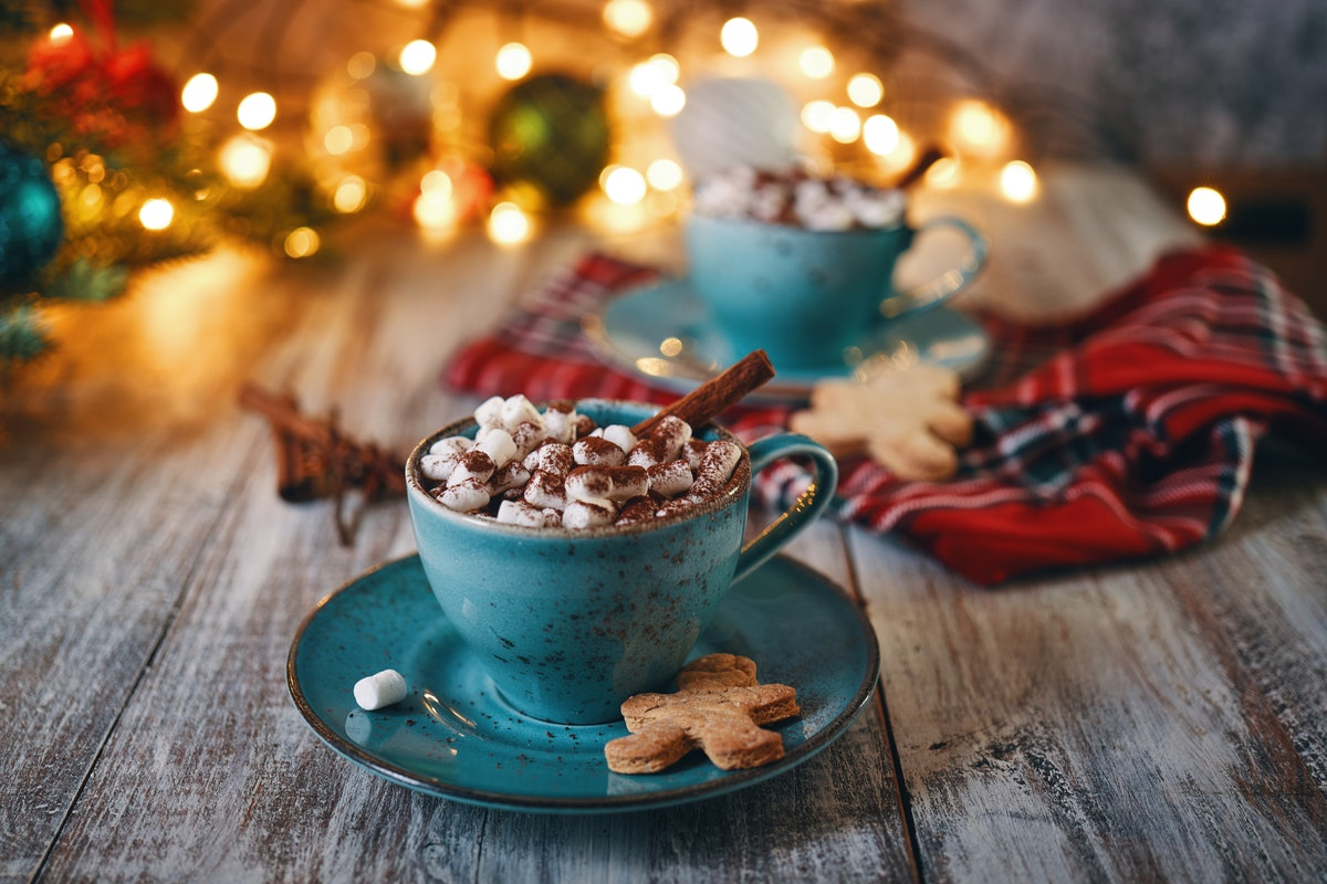 A holiday hot chocolate in a blue mug is placed on a wooden table with Christmas decorations all around.