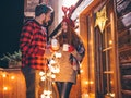 A couple dressed in festive clothing holds their holiday drinks while stringing up Christmas lights ...