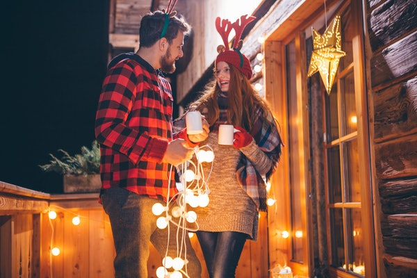 A couple dressed in festive clothing holds their holiday drinks while stringing up Christmas lights outside.