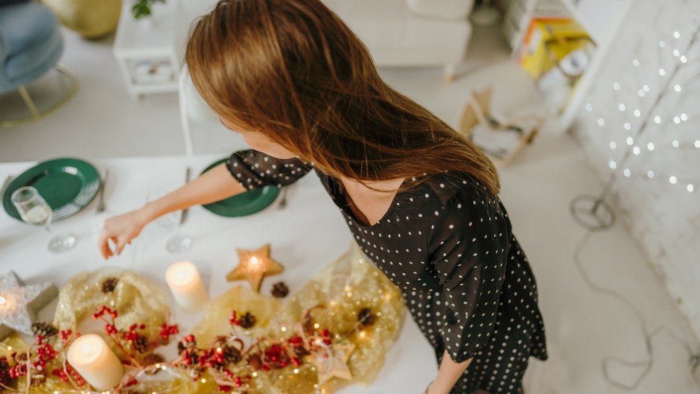 A woman sets up her New Year's Eve centerpiece with candles and a berry garland.