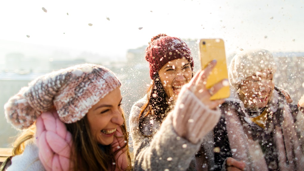 A group of women laugh while filming a snow day TikTok on a rooftop at golden hour.