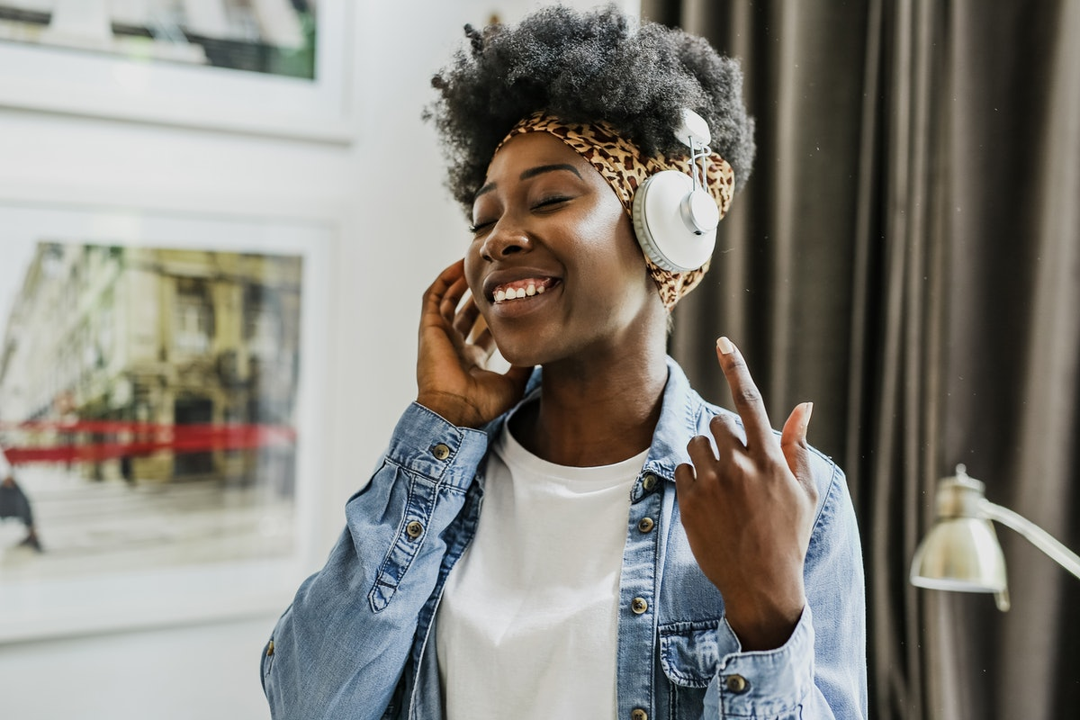 A happy woman with headphones on listens to music.