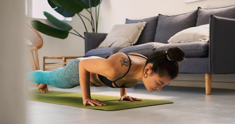 A woman does pushups in her living room. These lightweight workouts you can do anywhere.