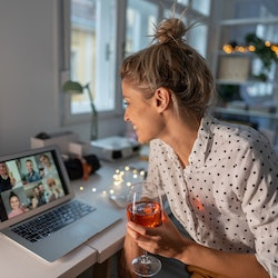 A woman has a glass of wine while on a Zoom call with family. These sneaky things can make hangovers...