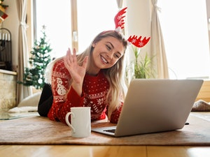 A woman in red reindeer antlers and a red sweater smiles at her virtual Christmas party on her laptop