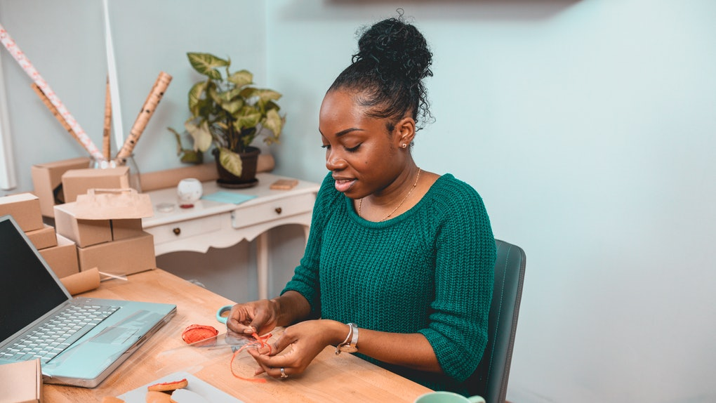 A young Black woman smiles while crafting gifts for the holidays and drinking tea.