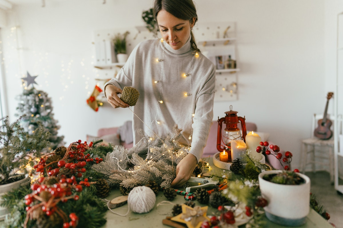 A woman wrapped in fairy lights crafts at her table to make Christmas ornaments for a merry artmas home