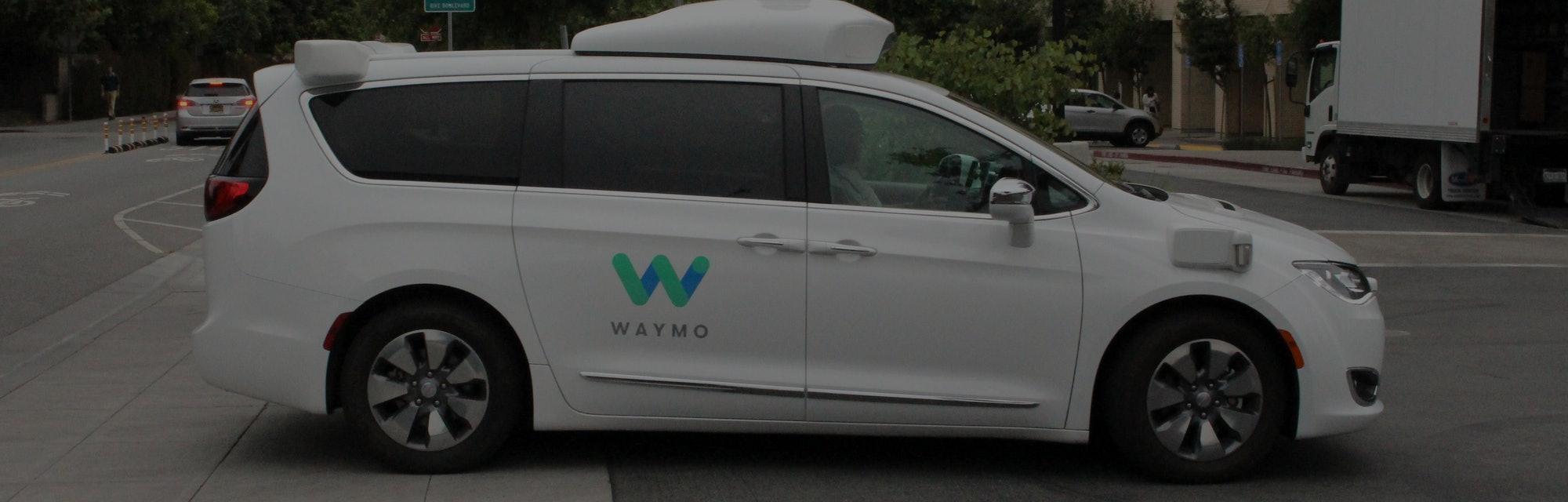 A Waymo autonomous van entering a parking lot.