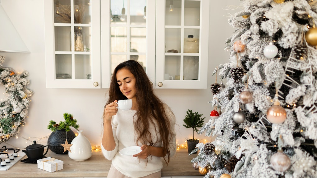 A woman enjoys her mug of coffee in a bright kitchen next to her decorated white Christmas tree.