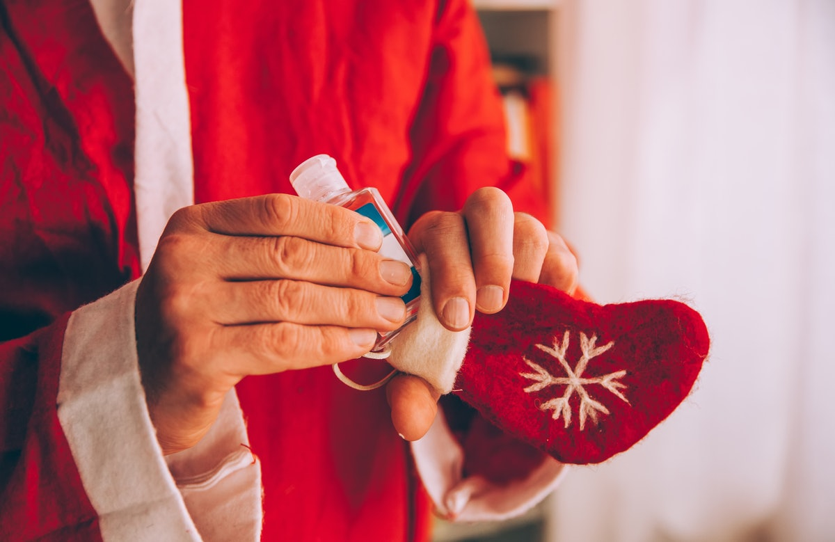A man is filling his stocking stuffer with a handy and sweet smelling holiday hand sanitizer