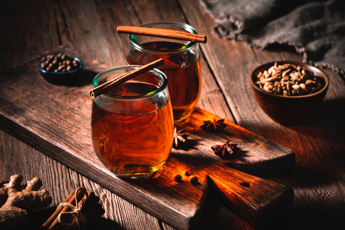 Two hot toddy drinks sits on a wooden board with cinnamon sticks on top.