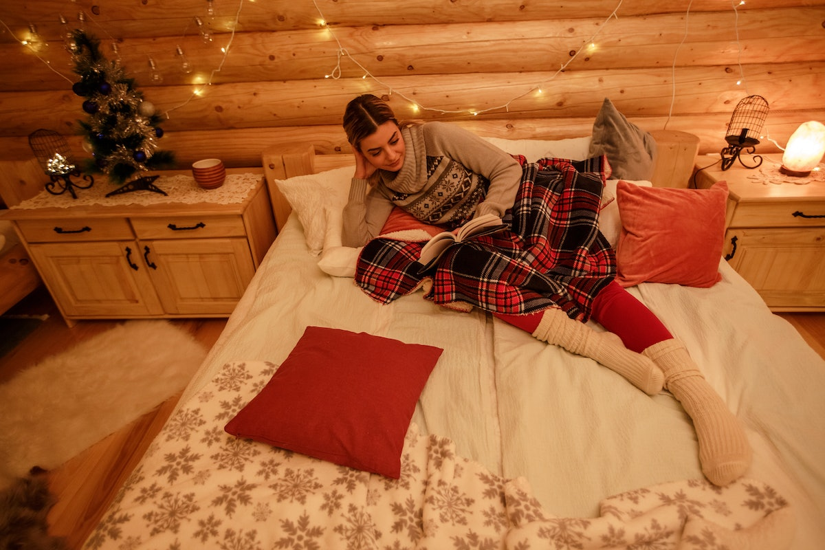 A young woman lounges in bed and reads a book while staying at a cozy cabin decorated for Christmas.