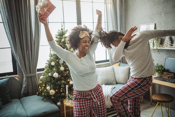 A couple dances around their living room on Christmas morning, wearing matching pajamas.