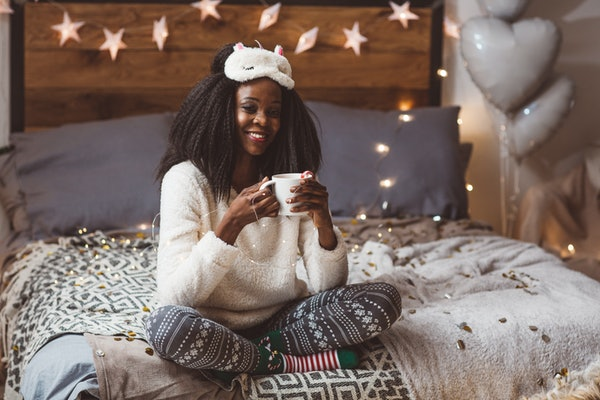 A happy woman wearing holiday loungewear, sips on hot cocoa, while relaxing on her bed.