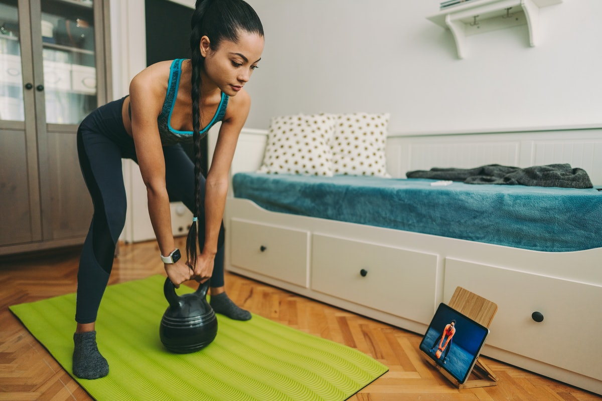 A woman does a kettlebell routine virtual workout at home. A ClassPass report reveals the most popular virtual workouts of 2020.