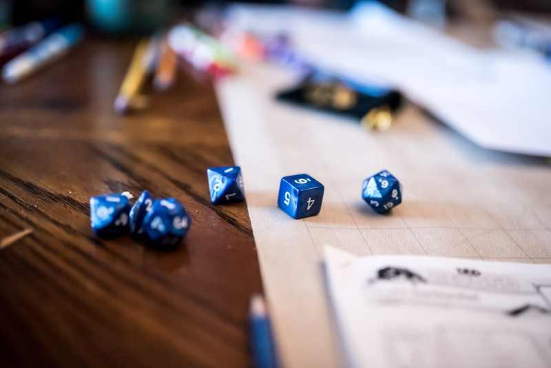 Various multi-sided dice in a dungeons and dragons game. How to play dungeons & dragons on zoom online.