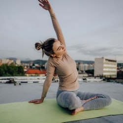 A woman does yoga on a roof. A ClassPass report reveals the most popular virtual workouts of 2020.