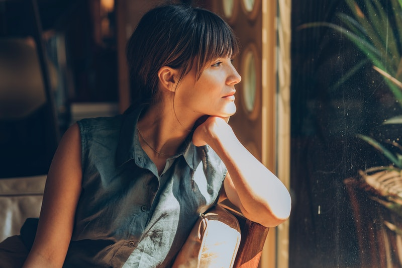 A woman stares out the window near a plant. Maladaptive daydreaming is all over TikTok's for you page. Here's what maladaptive daydreaming means and why it's grown during the pandemic.