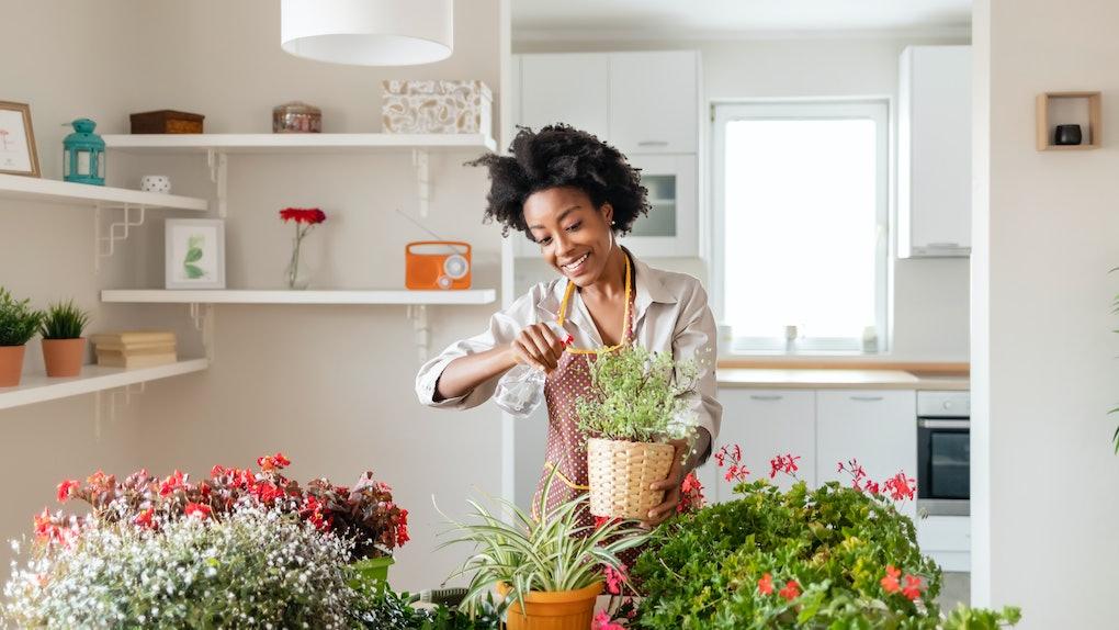 A crafty woman enjoys herself by potting some plants.