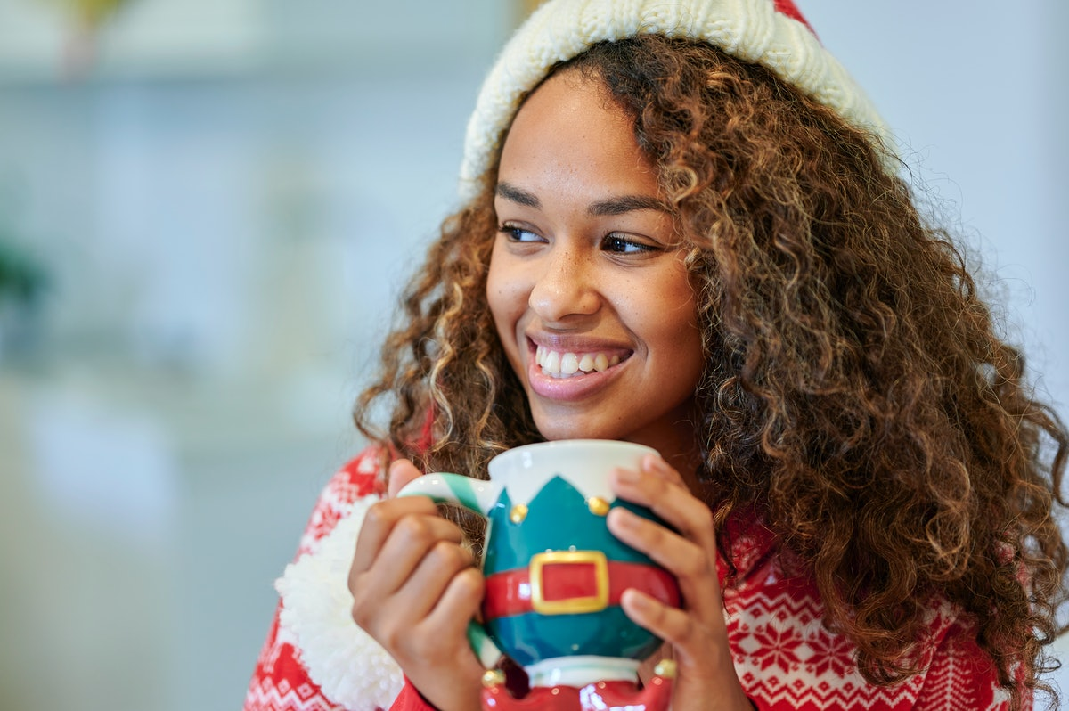 A happy woman in a holiday sweater smiles while holding her mug that has an elf design on it.