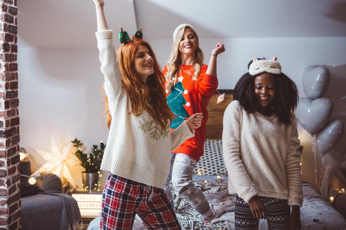Three friends in Christmas pajamas dance around their bedroom.