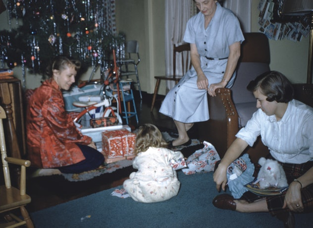 This vintage Christmas photo shows a family unwrapping gifts on Christmas morning.