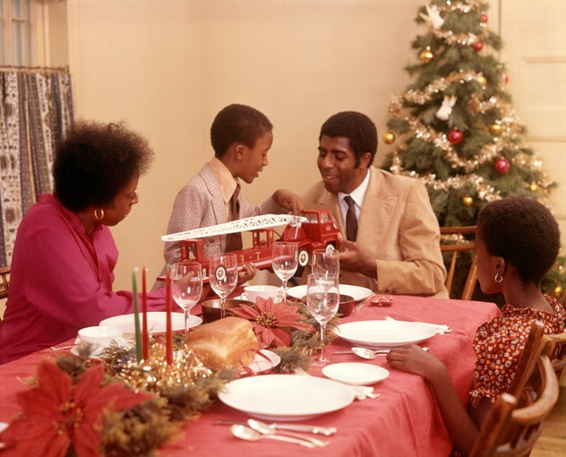 This vintage Christmas photo shows a family at their dining table.