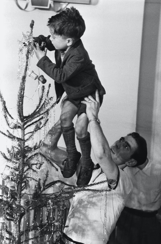 This vintage Christmas photo shows a man lifting up a boy to decorate their tree.