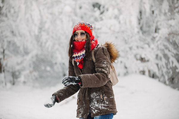 A happy woman bundled up for winter grabs snow to throw.