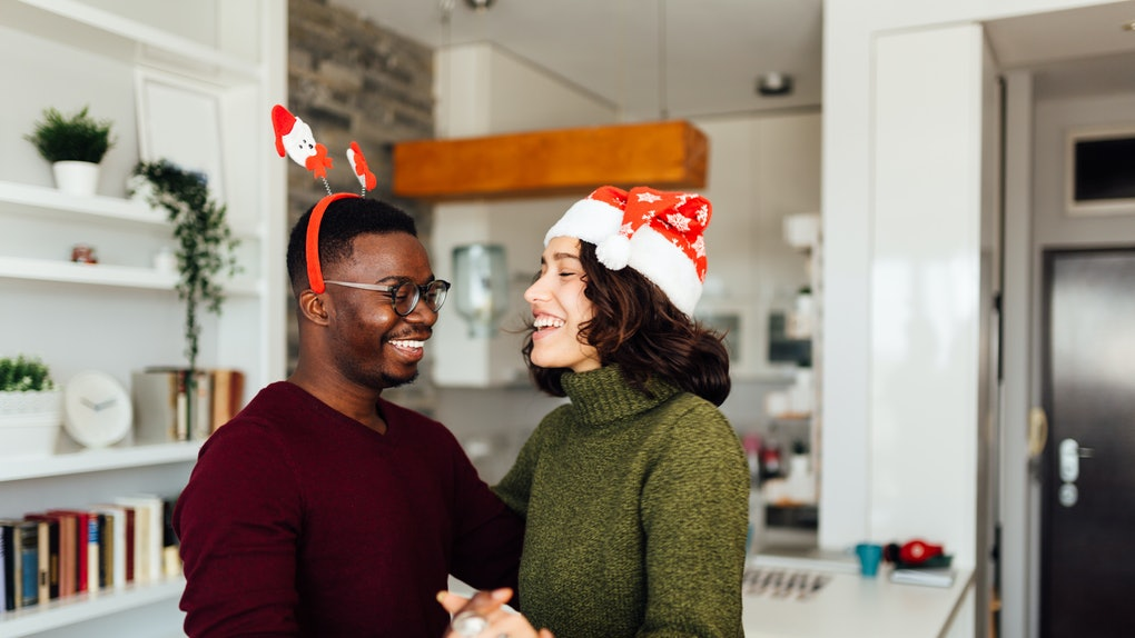 A happy couple dances in their home while listening to TikTok's 2020 Christmas songs.