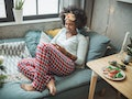 A happy woman in Christmas PJs relaxes on the couch next to her Christmas tree and a table that has ...