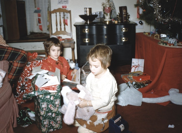 This vintage Christmas photo shows two children opening gifts.
