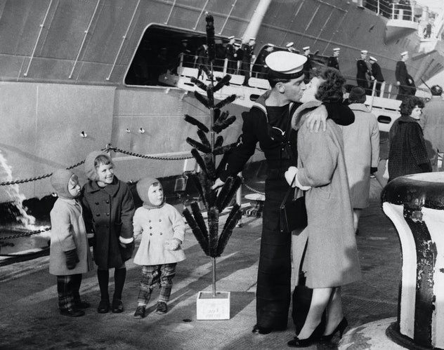 This vintage Christmas photo shows a family welcoming a sailor home for the holidays.