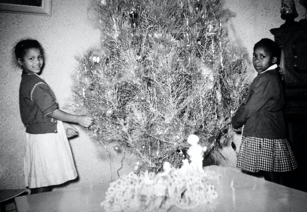 This vintage Christmas photo shows two girls decorating their tree.