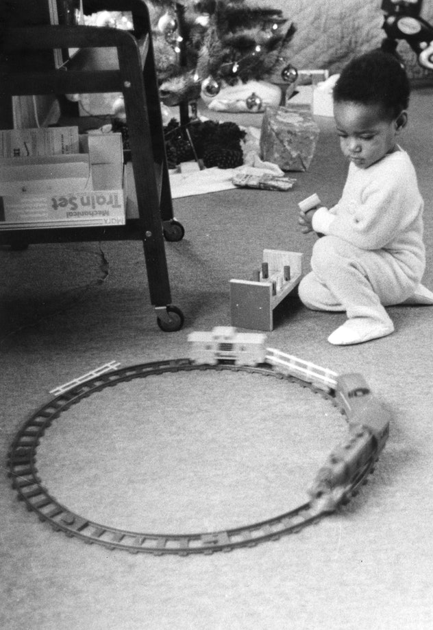 This vintage Christmas photo shows a little boy playing with a train set.