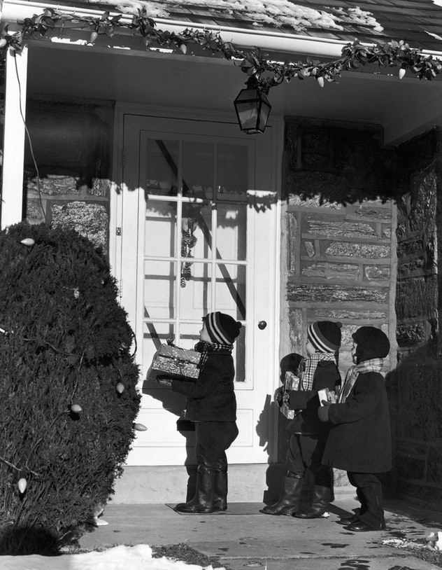 This vintage Christmas photo shows children delivering gifts to neighbors.