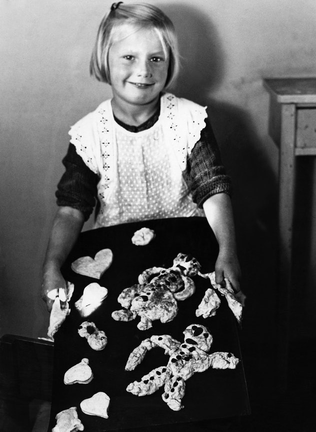 This vintage Christmas photo features a girl with Christmas cookies.