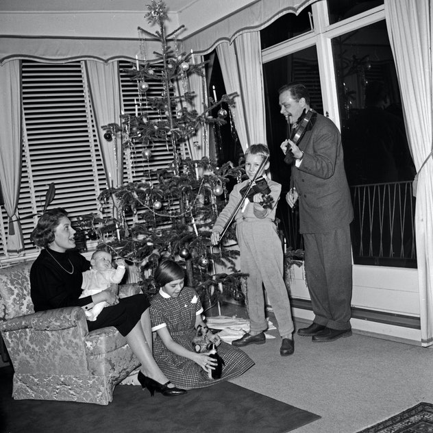 This vintage Christmas photo shows a family playing instruments around their tree.