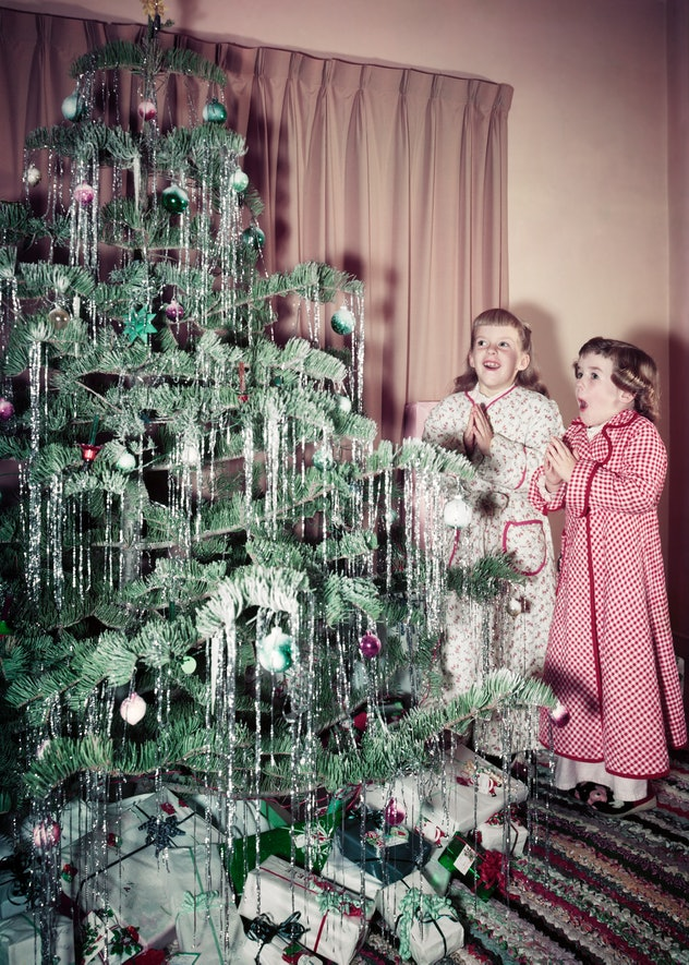 This vintage Christmas photo shows two girls in the 1950s admiring their tree.