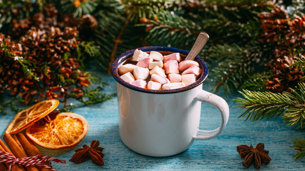 A hot chocolate sits on a table next to holiday table decor like cinnamon sticks and garland.