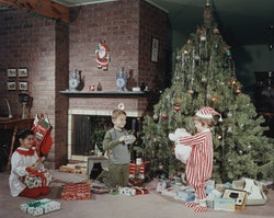 Children playing in front of the tree in this vintage Christmas photo is such a classic scene.