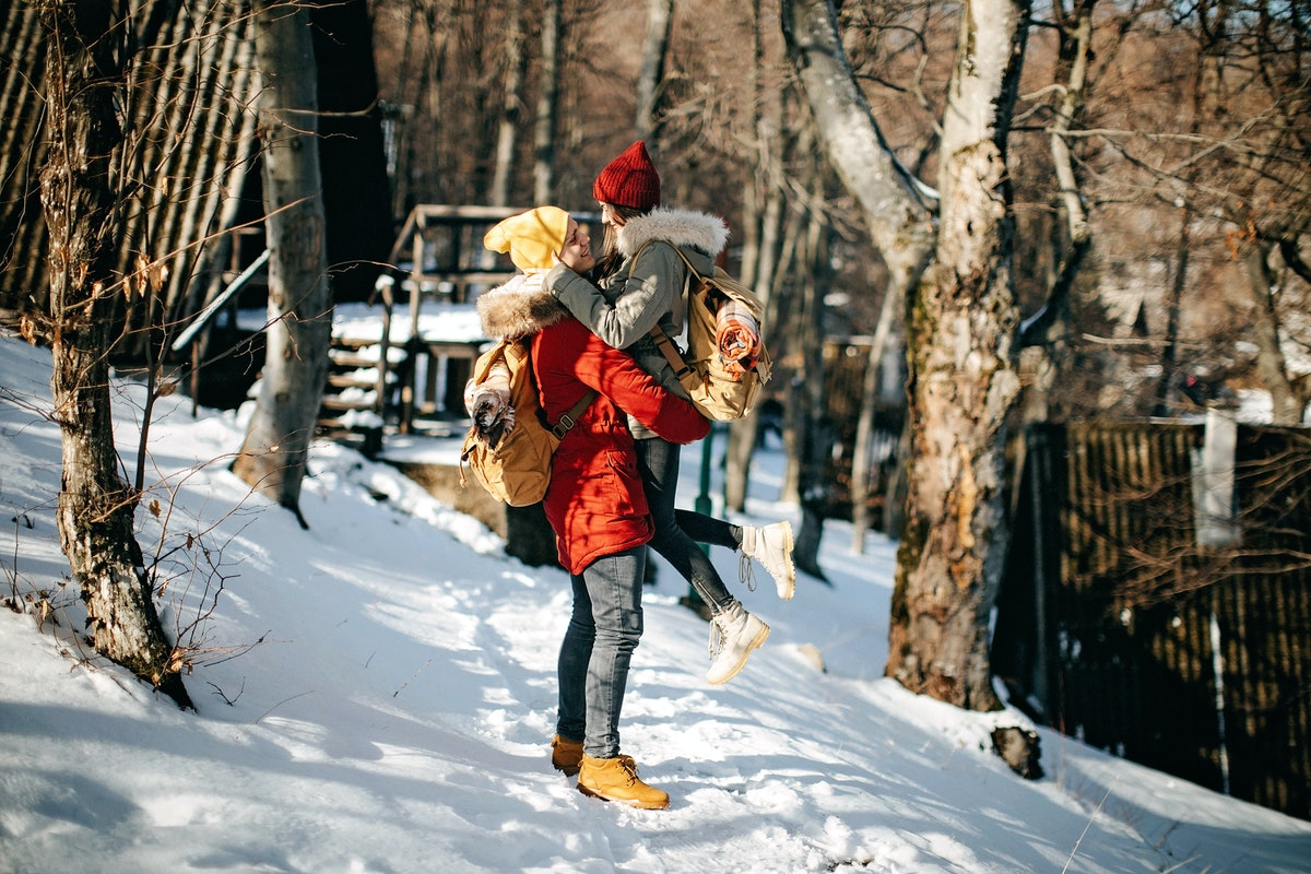 A happy couple embraces in the snow on a sunny day by a winter cabin.