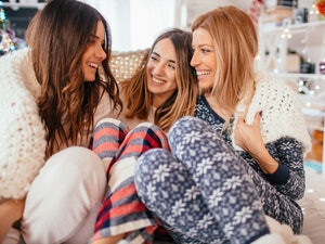 Three sisters on Christmas morning, snuggle together while wearing festive loungewear.