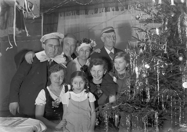 This vintage Christmas photo from 1938 shows a family near their tree.